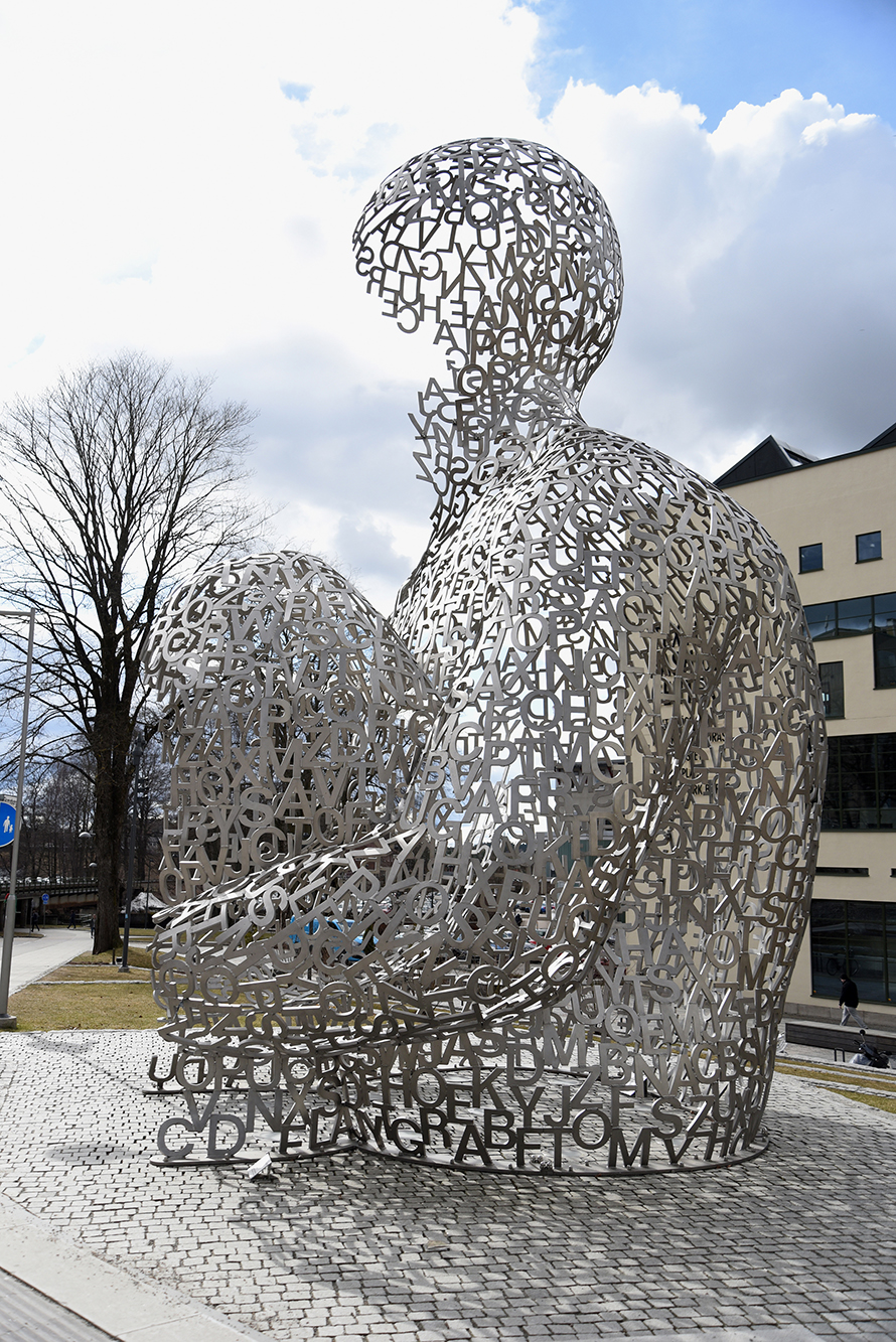8 meters high sculpture depicting a crouching human figure made of silver-colored letters.